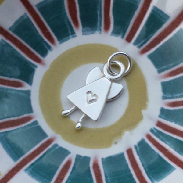 Skruttängel 7 - ett silverhänge i form av en ängel med hjärta mitt fram och små knubbiga ben. 18 x 10 mm. Cirkelformad bakgrund i bl a gult och grönt.