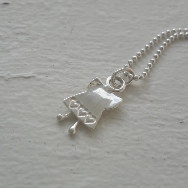 Silverängel med en hjärtkantad kjol mot vit bakgrund.