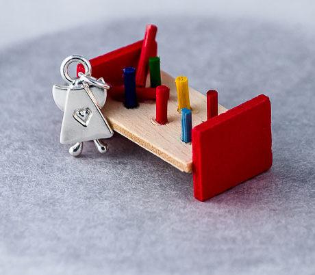 Silverberlock i form av en ängel med hjärta mitt fram och små knubbiga ben, stående framför en röd dockhusleksak.. 18 x 10 mm. Kallas Skruttängel 7