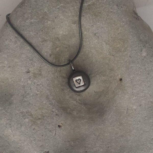 Kärleksbomb - runt, mörkt oxiderat silverhänge med kedja, liggande på grå sten.