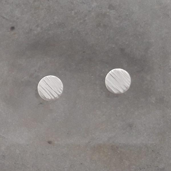 Randigt mönstrade silverörhängen mot grå bakgrund. Görs i tre storlekar, 8, 10 och 12 mm.