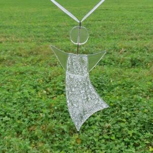 En lätt vitmönstrad ängel av återvunnet fönsterglas - en Gladängel. Hängande i vitt medföljande band mot grön bakgrund. Ca 20 cm.