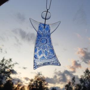 Gladängel 5 - en handgjord glasängel av återvunnet fönsterglas. Ängeln har ett blått spetsmönster och är delvis transparent. Gladängeln är ca 20 cm och ett vitt band att hänga upp den i medföljer. Himmel i bakgrunden.