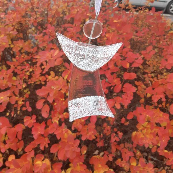 Gladängel 7 - en handgjord glasängel av återvunnet fönsterglas. Ängeln har ett spetsmönster upptill och nedtill och är delvis transparent. Gladängeln är ca 20 cm och ett vitt band att hänga upp den i medföljer. Ses mot bakgrund av röda blommor.