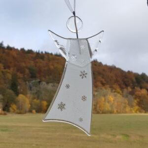 Gladängel 8 - en handgjord glasängel av återvunnet fönsterglas. Ängeln är vit och har ett mönster med snöstjärnor. Gladängeln är ca 20 cm och ett vitt band att hänga upp den i medföljer. Höstlandskap i bakgrunden.