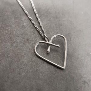 Unikt hjärta gjort för hand av silvertråd mot grå bakgrund.