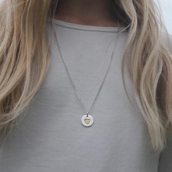 Rund silverberlock med guldhjärta, 14 x 14 mm.