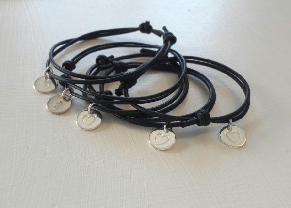 Svarta armremmar med handgjord silverberlocker, de flesta med hjärtan.