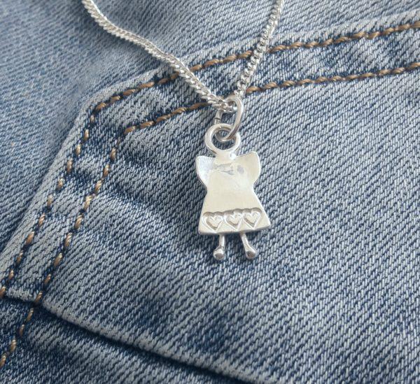Silverängel med en hjärtklädd kjol på ett par slitna jeans.