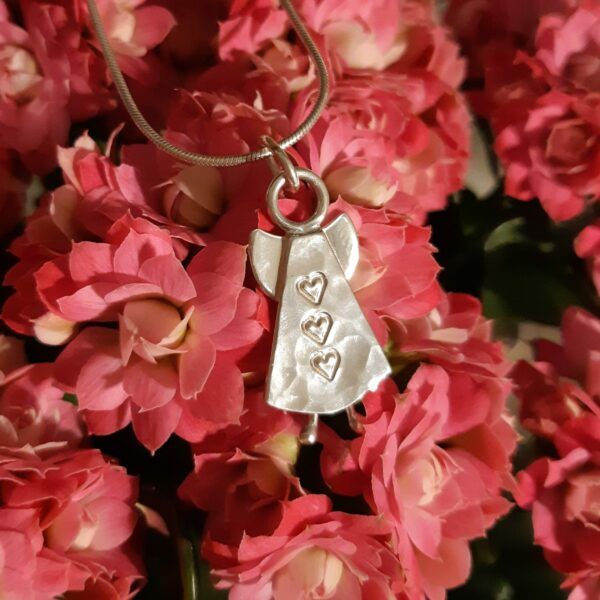Silverängel med hamrad yta och tre instansade hjärtan på lodrät rad mot rosaröd bakgrund.. 27 x 13 mm.