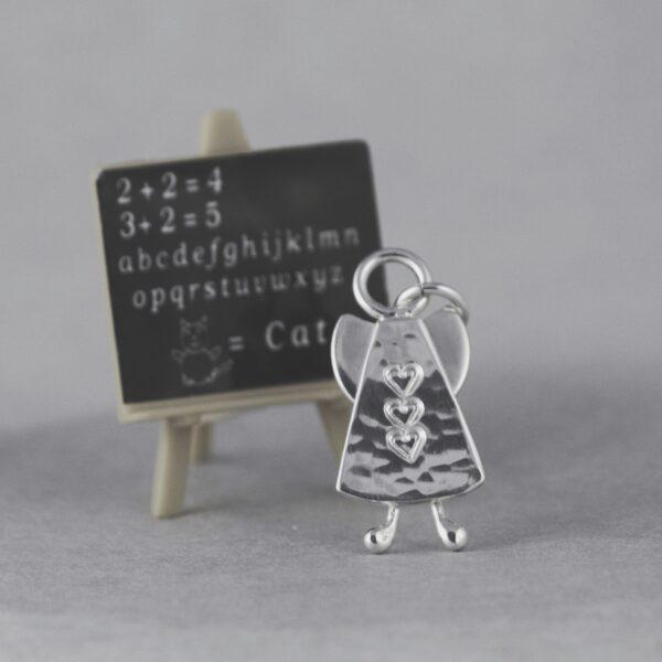 Skruttängel 3 - en handgjord silverängel med hamrad yta, tre instansade hjärtan på lodrät rad, knubbiga små ben. Halsberlocken lutar sig mot en liten griffeltavla. mot27 x 13 mm.