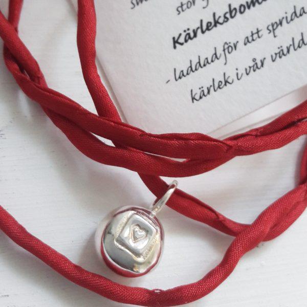 Kärleksbomb - ett runt massivt silverhänge med instansat hjärta i röd rem. Ljus bakgrund med del av en text upp till höger på bilden.