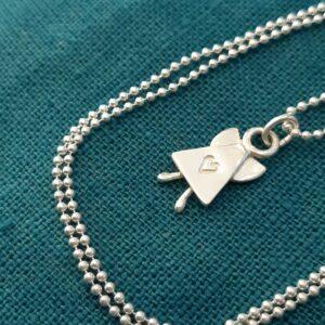 Skruttängel 7 - en silverängel i halskedja liggande mot turkos bakgrund. Ängeln har små kbubbiga ben och ett instansat hjärta mitt fram. 18 x 10 mm.