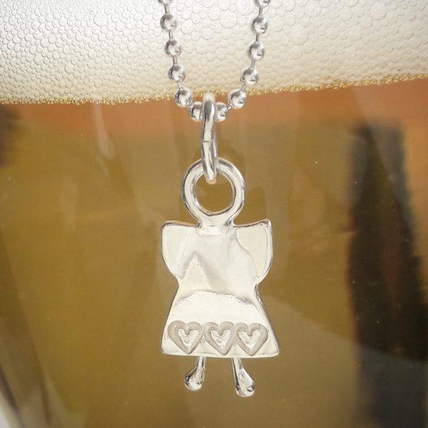 S med tre med tre instansade hjärtan nedtill hängande i en halskedja mot gul bakgrund. 18 x 10 mm
