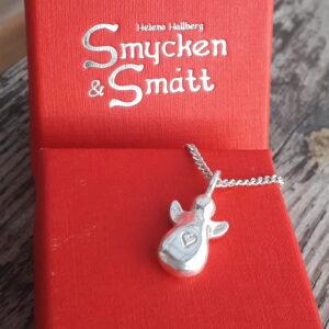 Massiv liten knubbig silverängel med instansat hjärta mitt fram,. Halssmycke liggande på röd ask med silvervit logga upptill.