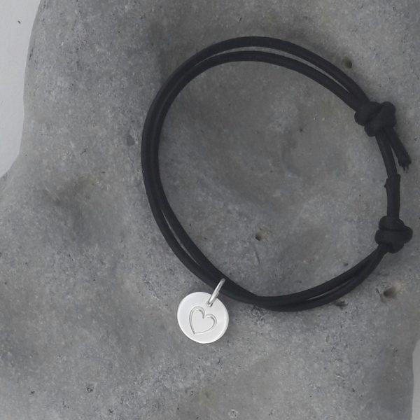 Rund silverberlock med instansat hjärta i svart armrem mot grå bakgrund.