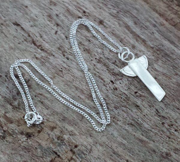 Skruttängel 5 - en stilren silverängel med halskedja liggande på grå bräda. 31 x 14 mm.