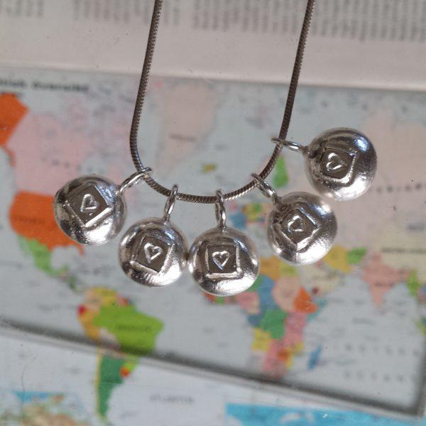 Fem Kärleksbomber på rad, massiva silverhängen mot bakgrund av världskarta.