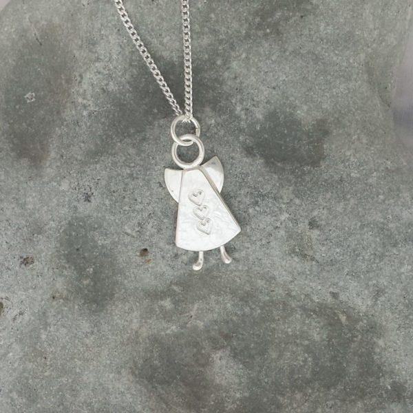 Handgjord silverängel med hamrad yta , tre små hjärtan på rad och knubbiga små fötter mot grå bakgrund.
