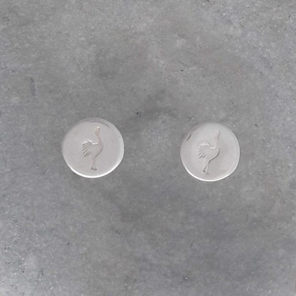 Runda handgjorda silverörhängen med instansade tranor mot grå bakgrund.