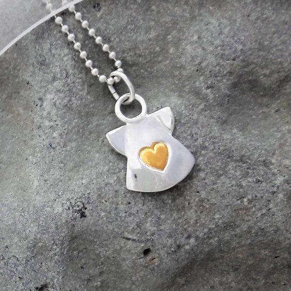 Silverängel med ett hjärta av guld mitt fram, mot grå bakgrund. Halssmycke i silverkedja. 20 x 14mm.