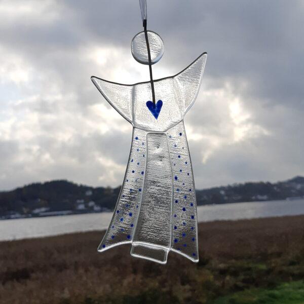 Gladängel 2 - en handgjord glasängel av återvunnet fönsterglas. Ängeln har ett mönster i form av ett blått hjärta och prickar. gladängeln är ca 20 cm och ett vitt band att hänga upp den i medföljer.