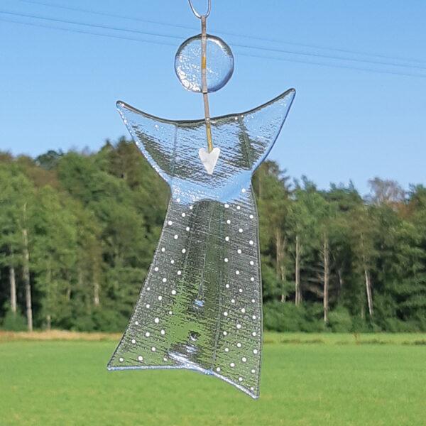 Gladängel 4 - en handgjord glasängel av återvunnet fönsterglas. Ängeln har ett mönster i form av ett vitt hjärta och prickar och är delvis transparent. Gladängeln är ca 20 cm och ett vitt band att hänga upp den i medföljer. Gräs, träd och himmel i bakgrunden.