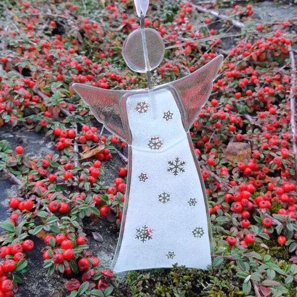 Gladängel 8 - en handgjord glasängel av återvunnet fönsterglas. Ängeln är vit och har ett mönster med snöstjärnor. Gladängeln är ca 20 cm och ett vitt band att hänga upp den i medföljer.