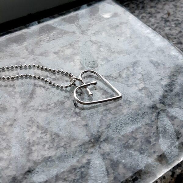 Handgjort hjärta av silvertråd, ett halssmycke i silverkedja, 22 x 20 mm.